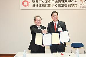協定書調印式にて山崎善也綾部市長と握手を交わす古山学長(写真左)