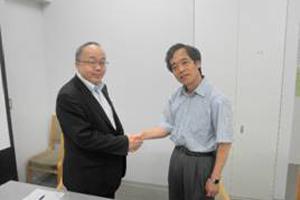 握手を交わす牛田校長と播磨教授